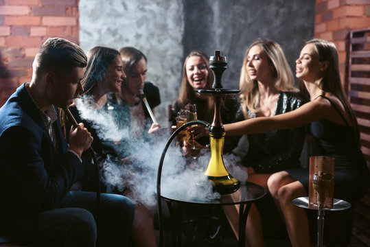 Friends party in hookah lounge. Group of people women and men smoking shisha in cafe or bar, making smoke clouds, having fun, smiling. Relax concept. Friendship