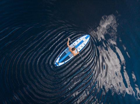 Man rowing oar on sup board blue sea water. Aerial top view paddleboard