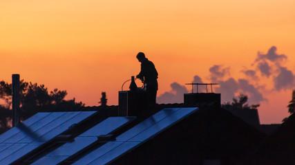 Männliche silhouette im Abentrort auf einem Dach bei reinigen des Schornstein
