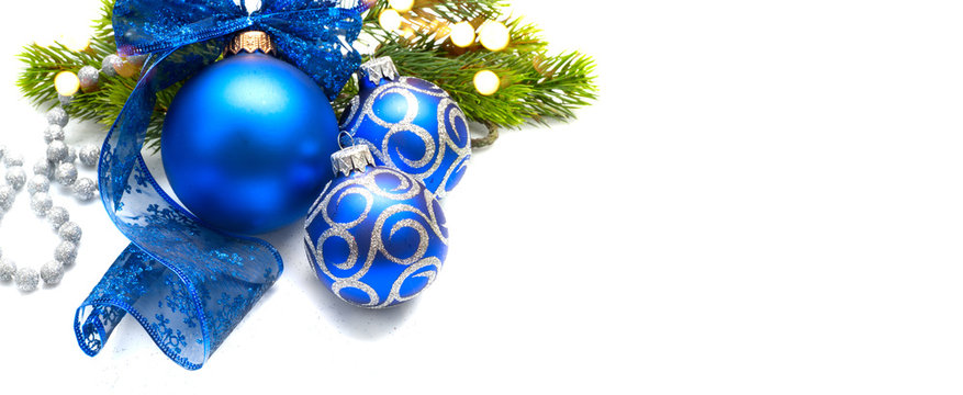 Blue Christmas and New Year Decoration isolated on white background. Border art design with holiday baubles. Beautiful Xmas tree closeup decorated with balls, tinsel, ribbon. Space for text