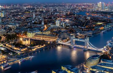 Blick auf die beleuchtete Skyline von London am Abend mit Tower Bridge und modernen Bürogebäuden entlang der Themse