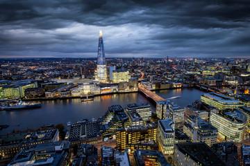 Fotomurales - Blick auf die markante Stadtlandschaft von London am Abend mit bewölktem Himmel und beleuchteten Gebäuden entlang der Themse