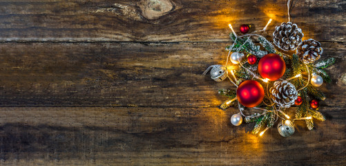 Christmas decoration banner with ornaments, green branches, fir cones and christmas lights on wood background with copy space