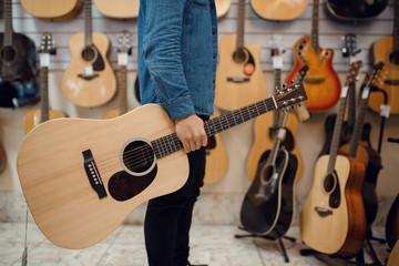 Spoed Foto op Canvas Muziekwinkel Young man holding acoustic guitar in music store