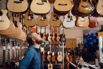 Poster Music store Young guy choosing acoustic guitar in music store
