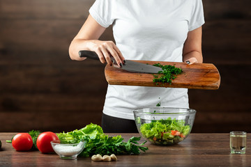 Woman cook cuts vegetables for salad preparation on a wooden background. Proper healthy eating.