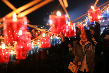 People light up candles to be released with the hot-air balloon during the Tazaungdaing Lighting Festival at Taunggyi,