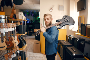 Tuinposter Muziekwinkel Man poses with electric guitar in music store