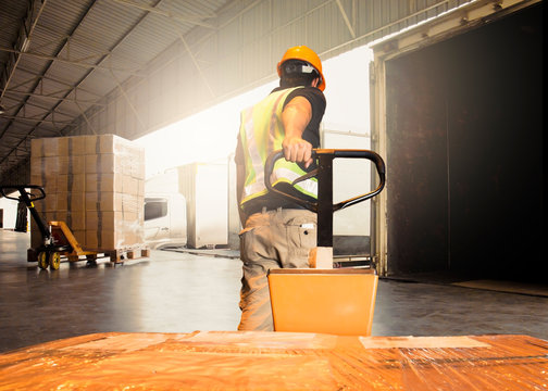 Warehouse worker unloading pallet shipment boxes into cargo container. Pakage boxes. Shipping warehouse logistics. Freight truck transportation.