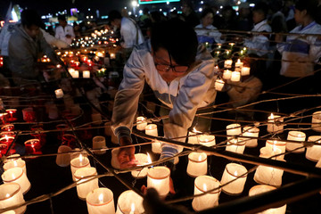 People light up candles to be released with the hot-air balloon during the Tazaungdaing Lighting Festival at Taunggyi