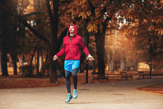 Man jumping rope outdoors on sunny autumn morning.