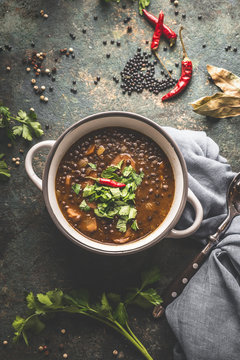 Black lentil soup in soup bowl on dark table background with spoon. Healthy vegetarian or vegan food concept. Top view