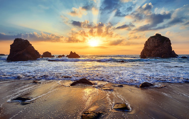 Printed kitchen splashbacks Sea sunset Sand beach among rocks on evening sunset. Ursa Beach near Cape Roca (Cabo da Roca) at Atlantic Ocean coast in Portugal. Summer landscape.
