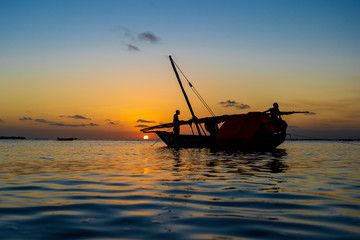Traditional fisherman dhow boat during sunset on Indian ocean in island Zanzibar, Tanzania, East Africa