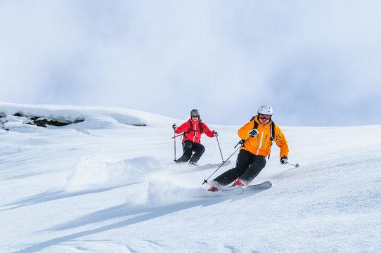 Zwei Skifahrer befahren gemeinsam einen steilen Hang