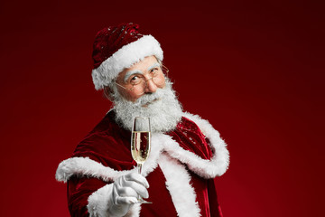 Waist up portrait of smiling Santa Claus holding champagne glass while standing over red background, copy space