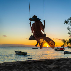 Papiers peints Zanzibar Beautiful girl in a straw hat and pareo swinging on a swing on the beach during sunset of Zanzibar island, Tanzania, Africa. Travel and vacation concept