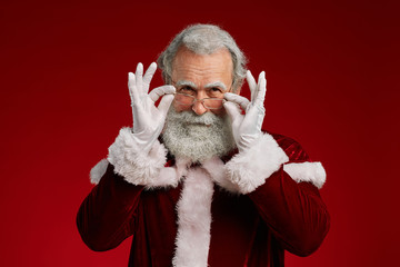 Waist up portrait of classic Santa Claus looking at camera and adjusting glasses while posing...