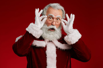 Waist up portrait of surprised Santa Claus looking at camera and adjusting glasses while posing against red background in studio, copy space