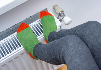 A child wearing wool orange-green socks warm his frozen legs on heater. The symbolic image of a house heating system in the winter col