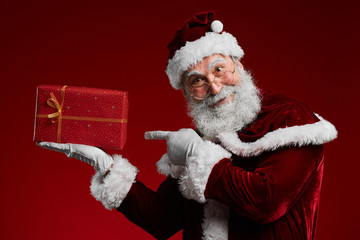 Waist up portrait of classic Santa Claus pointing at Christmas present while standing against red background in studio