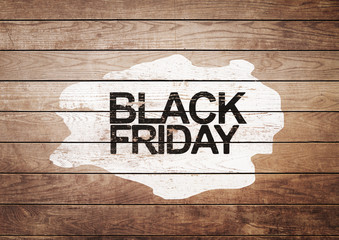 Black Friday sign on white painting and wooden background