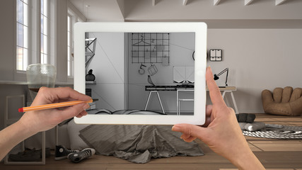 Hands holding and drawing on tablet showing modern white bedroom with bed details CAD sketch. Real finished interior in the background, architecture design presentation