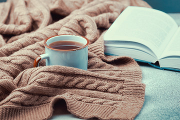 Сup of hot tea, open book and warm knitted blanket
