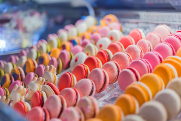 Dessert, biscuit, sweet food and traditional french cuisine concept. Assortment of colorful macarons cakes for sale on counter of candy shop, market, cafe or bakery. Rows of bright colors macaroons.