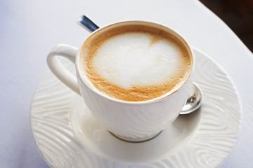 Fotobehang - A cup of fresh cappuccino in caffe close-up