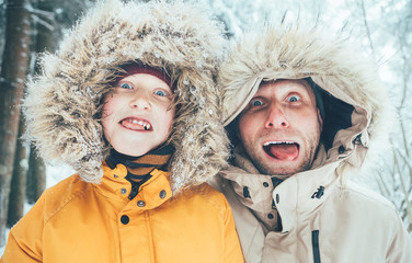 Father and son fooling into the camera. They showing their tongues and making grimaces. Parent and children winter holidays spending concept image.