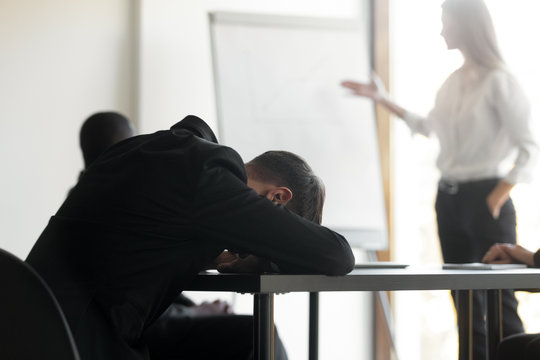 Tired male employee fall asleep at office meeting