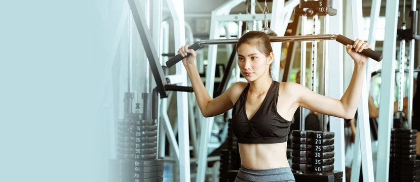 Portrait of beautiful Asian women wearing sportswear, playing weightlifting in gym workout shoulder muscles. Exercise makes the body healthy And have good body. lifestyle of modern people. copy space