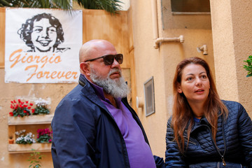 Carla Luccarelli and Angelo Di Ponzio, parents of a 15-year-old boy who died from a soft tissue sarcoma in January, speak during an interview, with a banner showing a portrait of their son in the background, in Taranto