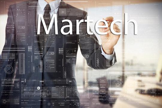 businessman writes a popular buzzword on a virtual whiteboard: Martech.