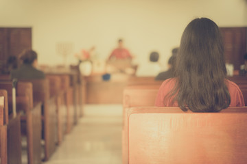 Back view of Girl in Church.Church Congregation Service and Christian worship.church interior background.vintage tone.