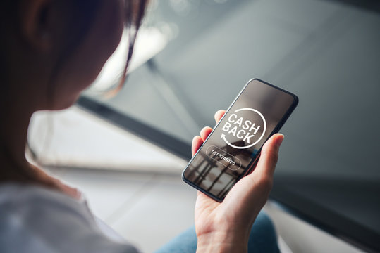 Shopping and Cashback concept, Money refund, Woman hand holding smartphone with button get started the cashback.