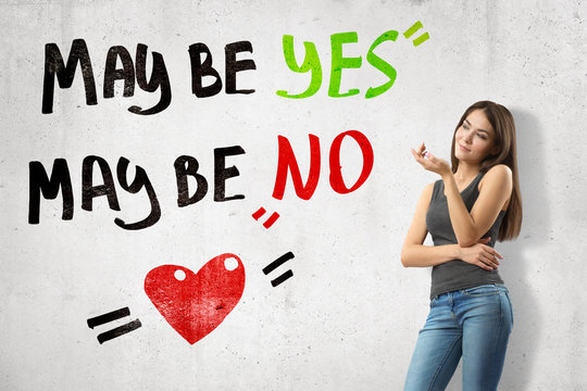 Young thinking brunette girl wearing casual jeans and t-shirt with 'Maybe yes maybe no' sign and cartoon heart on white wall background