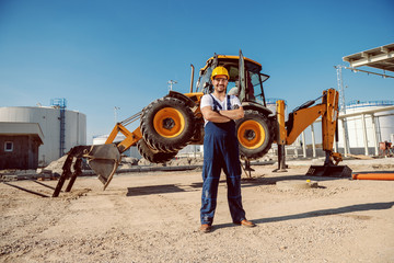 Handsome caucasian worker in overall and helmet on head standing outdoors with crossed arms. In background is excavator. Wall mural