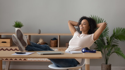 Satisfied African American woman relaxing with legs on table