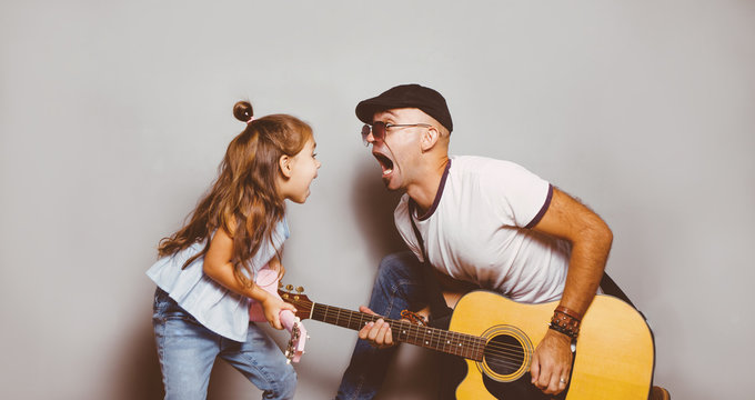 Beautiful little girl playing guitar with her father. Funny lifestyle picture. Happy family timespending. Girl holding pink ukulele ang singing and jumping,