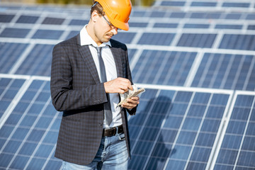 Businessman calculating money earned from the electricity production of a solar station. Concept of successful investment in alternative energy