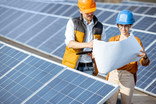 Two engineers or architects examining the construction of a solar power plant, standing with blueprints between rows of solar panels