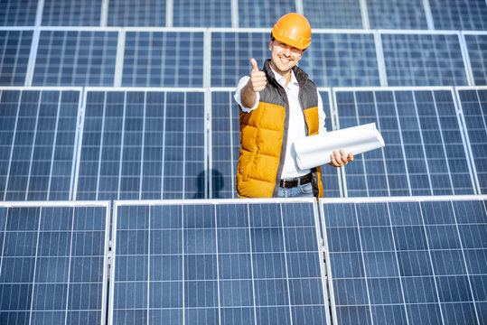 Portrait of a handsome engineer in protective helmet standing with blueprints on a solar power plant. Solar station development concept