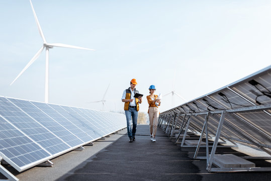 View on the rooftop solar power plant with two engineers walking and examining photovoltaic panels. Concept of alternative energy and its service