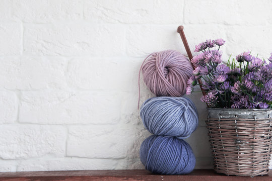 balls of cotton thread and a shabby old pot on a shelf, artificial flowers, decor elements.