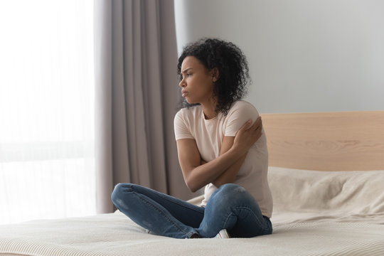 Upset sad African American woman sitting in bed alone