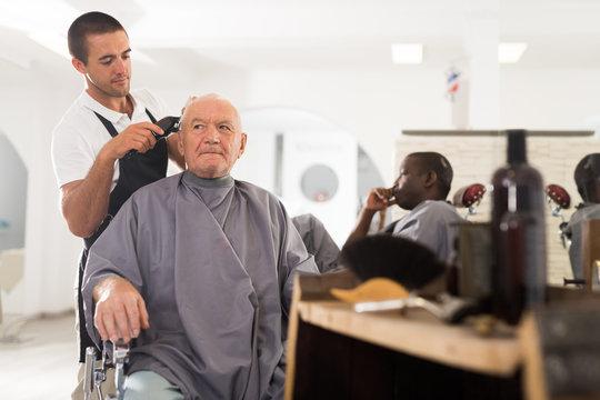 Elderly man getting haircut