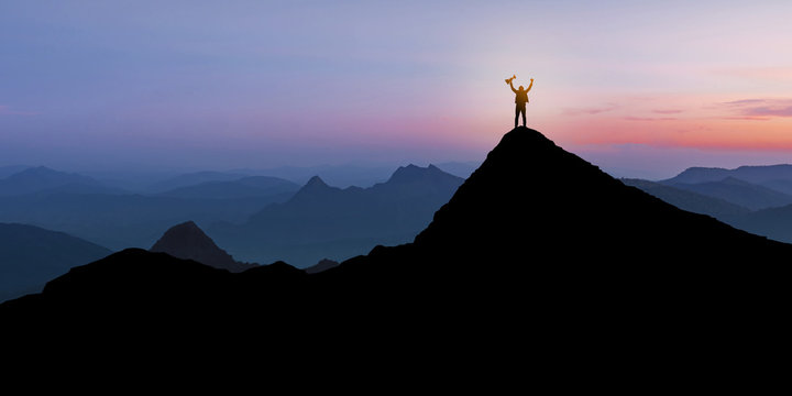 Silhouette of Businessman standing on mountain top over sunrise twilight background with holding up a trophy cup, Winner, Success and Leadership concept