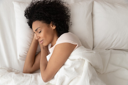 African American woman with hands under cheek sleeping in bed